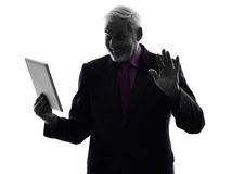 Senior business man holding digital tablet saluting silhouette Stock Photos