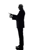 Senior business man holding digital tablet silhouette Royalty Free Stock Photography