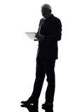 Senior business man holding digital tablet silhouette Royalty Free Stock Images