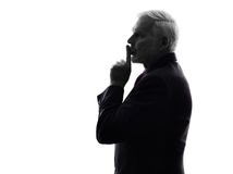 Senior business man hushing finger on lips silhouette Stock Photo