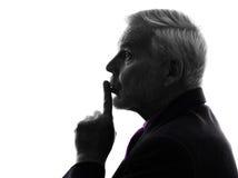 Senior business man hushing finger on lips silhouette Stock Photos