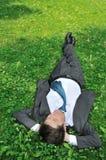 Senior business man lying in grass Royalty Free Stock Image