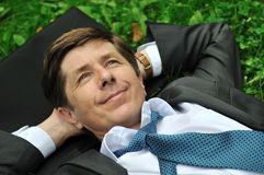 Senior business man lying in grass Stock Photography