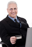 Senior business man making online purchase. With his credit card on white background Stock Photos
