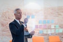 Senior business man making plans with sticker Stock Photos