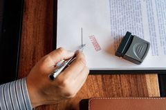 Senior business man male hand putting or signing signature in the certificate contract after approve stamp on loan document royalty free stock photo