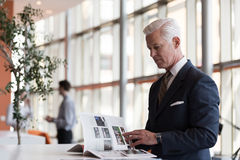 Senior business man reading magazine. At modern bright office stock photos