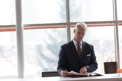 Senior business man reading magazine. At modern bright office royalty free stock photography