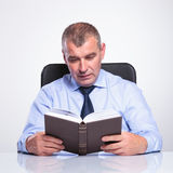 Senior business man reads at his desk Stock Image