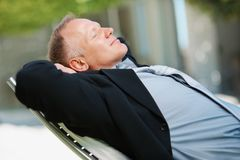 Senior business man relaxing on a recliner Stock Images