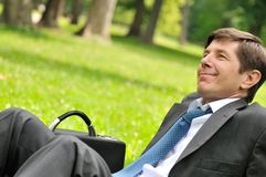 Senior business man siting in grass Stock Photo