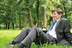 Senior business man siting in nature. Senior people series - mature business man siting on grass and relaxing in nature Stock Photo