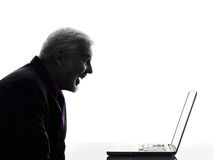 Senior business man smiling computing laptop silhouette Stock Photo