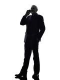 Senior business man on the telephone smiling silhouette Stock Images