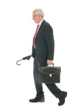 Senior business man walking with umbrella and bag Stock Images