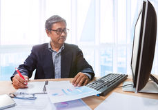 Senior business man working on office tabel with computer and bu. Siness graph report ,writing and thinking solution planing Royalty Free Stock Images