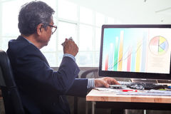 Senior business man working on office table with computer and bu Stock Image