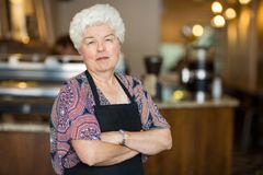 Senior Business Owner in Cafe. Portrait of beautiful senior female owner with arms crossed standing in cafe stock images