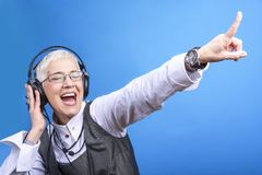 Senior business woman dancing to the beat of the music. Senior old woman listening to her favorite music through big headphones, enjoying the rich sound Royalty Free Stock Photos