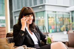 Senior business woman drinking mojito on phone Royalty Free Stock Photography