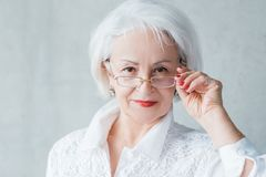 Senior business woman evaluative self assured lady. Senior lady portrait. Confident elderly female looking intently over glasses. Curious evaluative self assured royalty free stock images