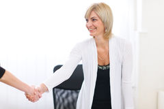 Senior business woman greeting visitor at office Stock Photos