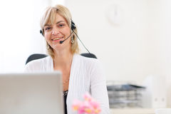 Senior business woman with headset using laptop stock photography