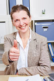 Senior business woman holding. Successful senior business woman in her office holding her thumb up Royalty Free Stock Photos