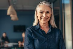 Senior business woman in office. Close up of senior business woman standing in office looking at camera and smiling. Mature female in office with team in stock photos