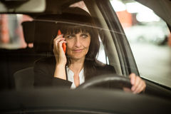 Senior business woman on phone driving car Royalty Free Stock Photo