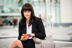 Senior business woman with phone in street Stock Photography
