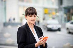 Senior business woman with phone in street Stock Image
