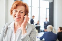 Senior business woman with smartphone stock photo