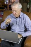 Senior businessman. In upscale home with laptop Royalty Free Stock Photos