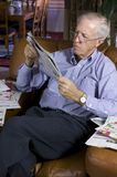 Senior businessman. Reading newspaper in upscale home Royalty Free Stock Photography