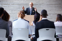 Senior Businessman Addressing Delegates At Conference Royalty Free Stock Images