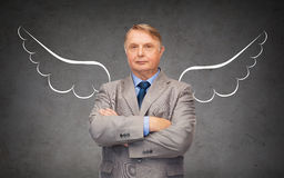 Senior businessman with angel wings over gray Stock Photography
