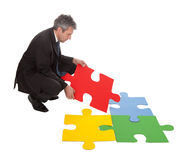 Senior businessman assembling a jigsaw puzzle Royalty Free Stock Photos