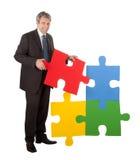 Senior businessman assembling a jigsaw puzzle Stock Image