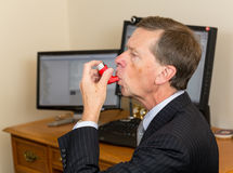 Senior businessman with asthma inhaler. Senior caucasian man  in suit at desk with computer screens with asthma inhaler to handle problems with breathing Stock Images