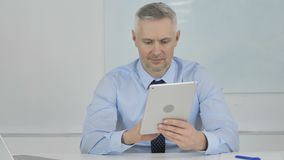 Senior Businessman Browsing Internet on Tablet in Office. 4k high quality, 4k high quality stock footage