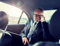 Senior businessman calling on smartphone in car stock image