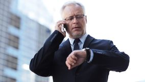 Senior businessman calling on smartphone in city stock footage