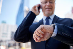 Senior businessman calling on smartphone in city. Business, technology, communication and people concept - senior businessman calling on smartphone and checking Stock Images