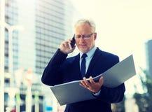 Senior businessman calling on smartphone in city stock photos