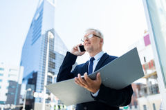 Senior businessman calling on smartphone in city Stock Photos