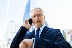 Senior businessman calling on smartphone in city. Business, technology, time, punctuality and people concept - senior businessman calling on smartphone an Royalty Free Stock Image
