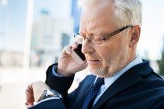 Senior businessman calling on smartphone in city Stock Photo