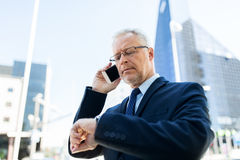 Senior businessman calling on smartphone in city. Business, technology, time, punctuality and people concept - senior businessman calling on smartphone an Royalty Free Stock Photography
