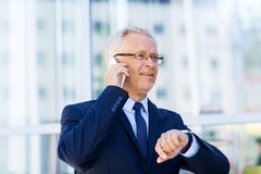 Senior businessman calling on smartphone in city. Business, technology, time, punctuality and people concept - senior businessman calling on smartphone with Stock Photo